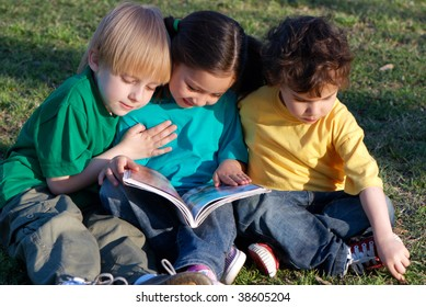 Group of children with the book on a grass in park