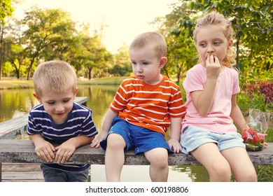 Group of children boys and girl enjoing together with strawberry on the bench at the country side