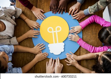 Group of children branstorming and sharing ideas with light bulb