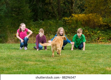 A group of children call a Golden Retriever puppy dog.  The dog is running towards them in a field of green grass.