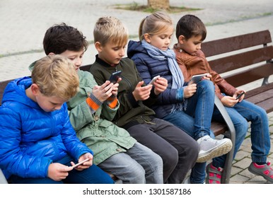 Group of children carried away with phone spending time together outdoors in autumn day