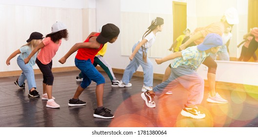 Group of children in casual clothes training hip-hop in class, learning modern dance movements