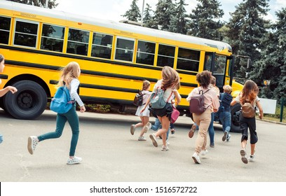 Group of children classmates runing to school bus back view late