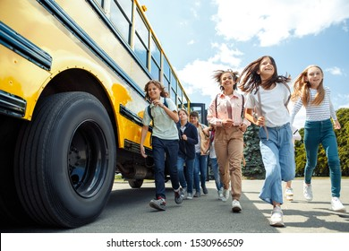 Group of children classmates running from school bus going back home looking forward smiling excited