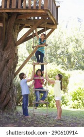 Group Of Children Climbing Rope Ladder To Treehouse