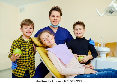 A group of children with a dentist a man smiling.