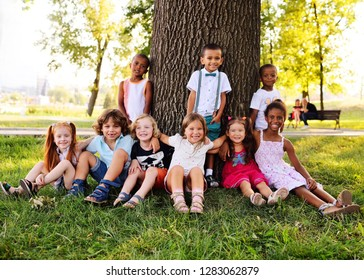 a group of children of different racial and ethnic types sit together under a big tree in the Park on the grass and smile.