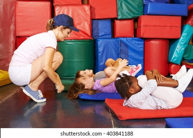 Group of children doing gymnastics in preschool with PE teacher