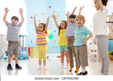 Group of children doing kids gymnastics in kindergarten or daycare