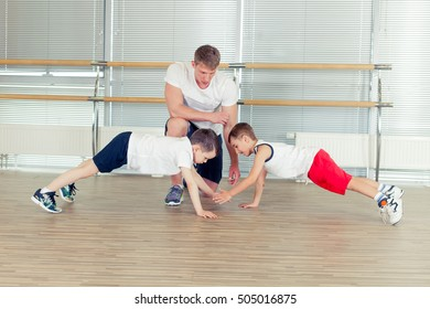 Group of children doing kids gymnastics in gym with nursery teac
