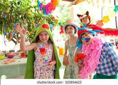 Group of children dressing up in improvised fancy dresses at a colorful birthday party in a home garden, party food and with joyful expressions, outdoors lifestyle. Kids activities and fun.