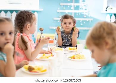 Group of children eating healthy food in kindergarten