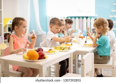 Group of children eating healthy food in day care centre