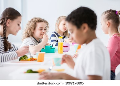 Group of children eating vegetables in the dining hall of school