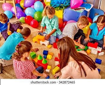 Group children game blocks and balloons on floor in kindergarten . Top view.