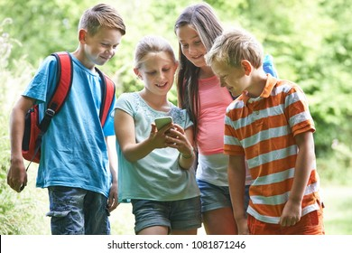 Group Of Children Geocaching Using Mobile Phone In Forest