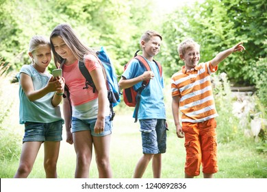 Group Of Children Geocaching In Woods