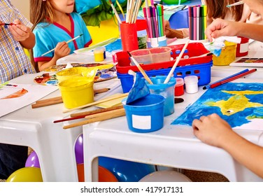 Group of children hands  painting on paper at table  in  kindergarten . Paint lesson.