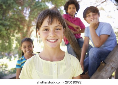 Group Of Children Hanging Out In Treehouse Together