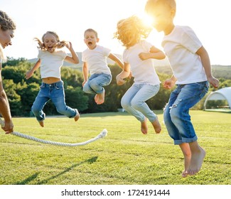 A group of children have fun playing in nature. Children jump over the rope. Warm summer evening with sunset light.