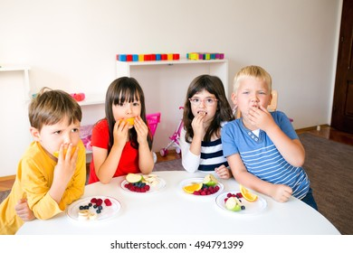A Group of children having fruit snack break in the kindergarten