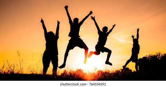 Group of children having fun jumps on sunset and sky backdrop silhouette.