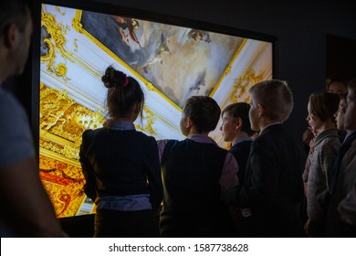 A group of children in an a history museum visiting the exhibition, interactive learning. Children use an interactive touchscreen display. St. Petersburg, Russia, Historical Park, November 24, 2019