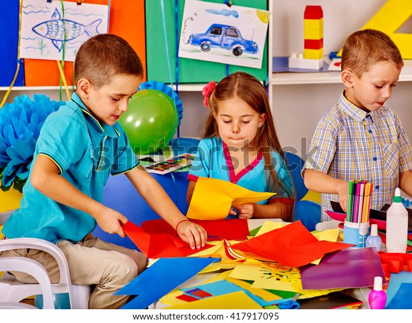 Group children holding colored paper on table in kindergarten . Children together work with paper in art class.