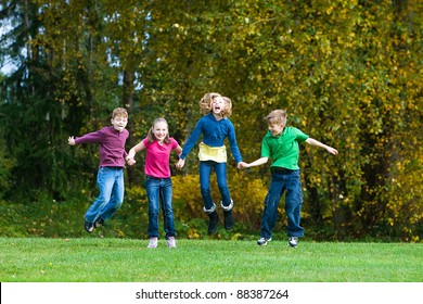 A group of children holding hands and jumping in the air.