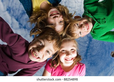 A group of children huddled up and looking down under a blue sky with high clouds.