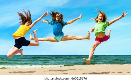A group of children jumping together on the beach