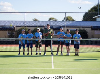 Group of Children Junior Teenage Tennis Players and Adult Coach in Front of Tennis Net on Court in Summer Weather