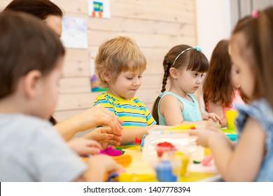 Group of children kids on art classes with teacher in kindergarten