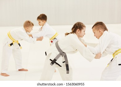 Group of children in kimono learning the technique of fight in group during lesson in karate in gym