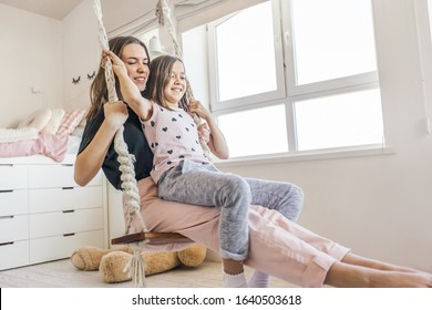 Group of children laughing and playing together, two girls having fun and swinging in bright scandinavian playroom. Kids paljamas party in white bedroom interior.