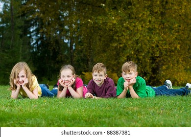 A group of children laying down in the grass.