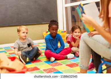 Group of children listen attentively while reading aloud from an exciting children's book