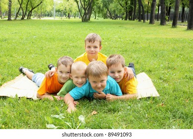 Group of children lying on the grass in the summer park