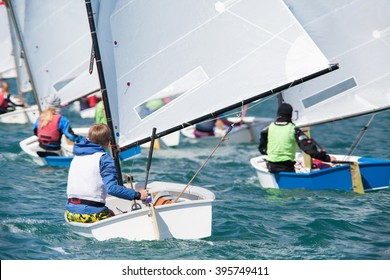 group of children on sailing boats competing in the regatta at sea