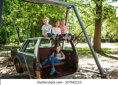 Group of children on a swing. Children playing outdoors in summer.