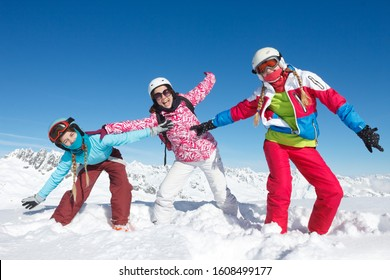 A group of children on winter sports holidays playing in the snow in good weather and blue sky