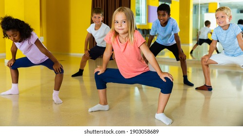 Group of children participating in dance class, following their teacher in dance school.