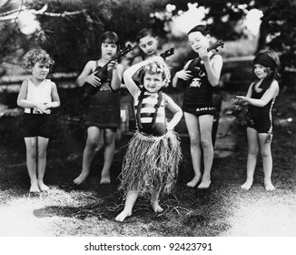 Group of children performing with instruments and one girl dancing the hula