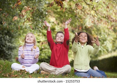 Group of children playing amongst autumn leaves in woodland