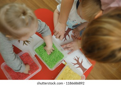 Group of children playing with colored rice from the sensory box. Painting exercise. Baby's sensory educational kit. Top view.