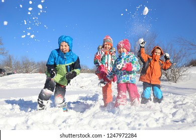 Group of children playing on snow in winter time