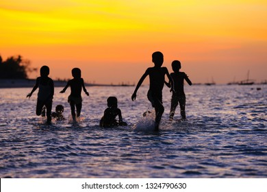 group of children playing in the water at sunset