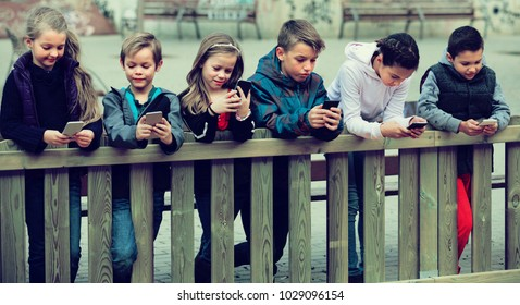 Group of children posing at urban street with mobile devices together