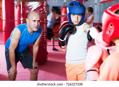 Group of children practicing with mentor on boxing ring at gym