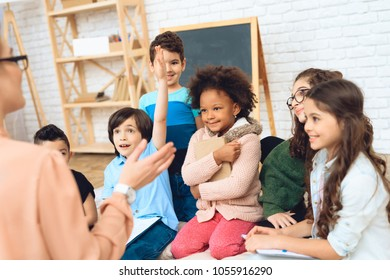 Group of children are pulling hands to answer teacher's question in primary school. Education of children in elementary school. Elementary School.